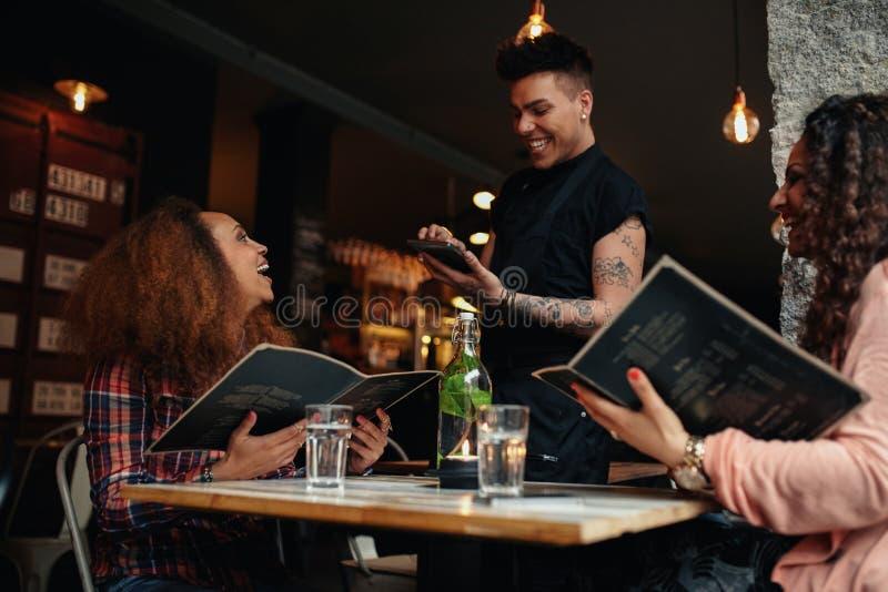 Jeunes femmes passant la commande à un serveur au café image stock