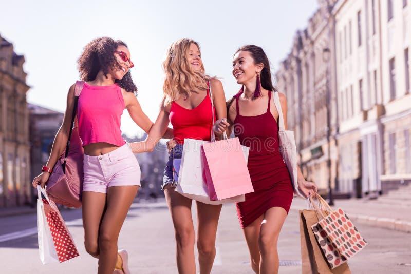 Jeunes femmes positives avec plaisir faisant l'achat ensemble photos stock