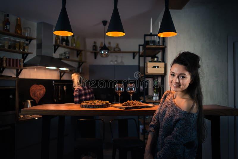 Jeunes femmes préparant le dîner dans la cuisine à la maison moderne le soir image libre de droits