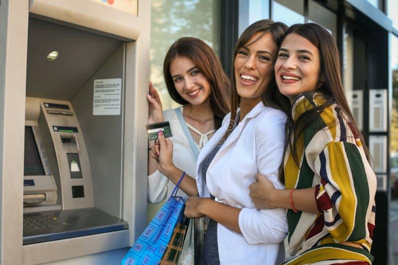Jeunes femmes prenant l'argent sur la machine d'atmosphère regarder l'appareil-photo photographie stock libre de droits