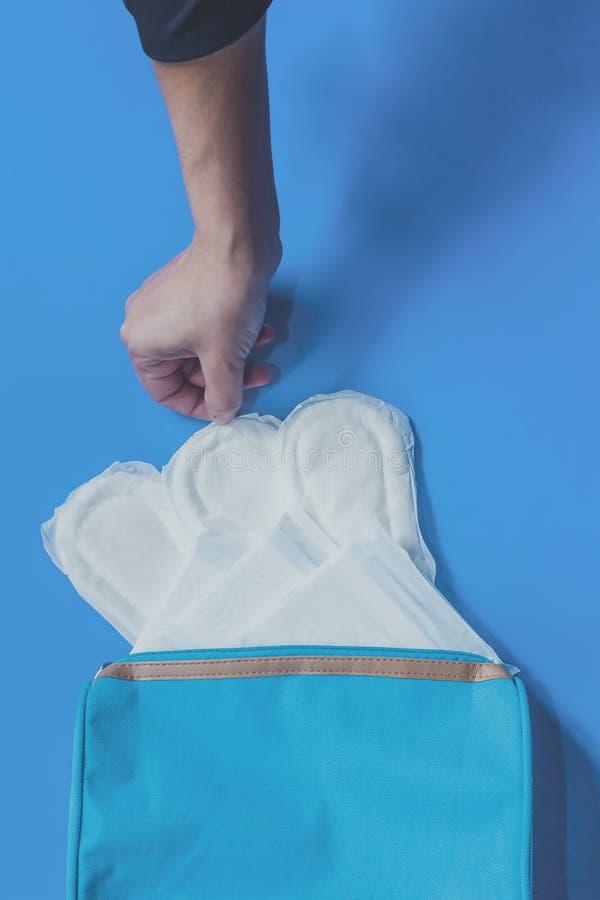 Jeunes femmes prenant les protections sanitaires ? l'int?rieur de son sac cosm?tique sur le fond bleu photos libres de droits