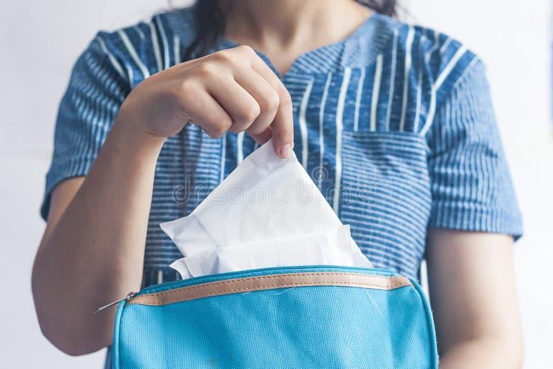 Jeunes femmes prenant les protections sanitaires ? l'int?rieur de son sac cosm?tique sur le fond bleu images stock