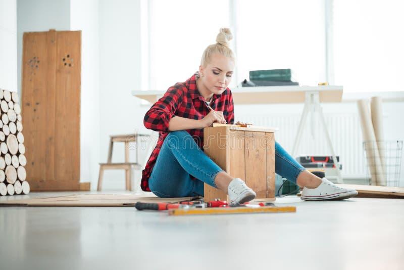 Jeunes femmes réparant des meubles à la maison image libre de droits