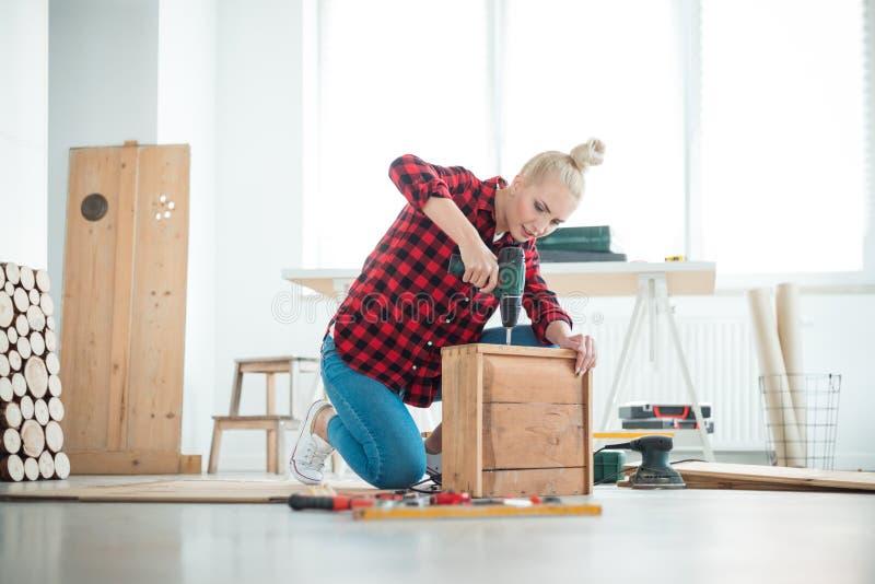 Jeunes femmes réparant des meubles à la maison photographie stock libre de droits