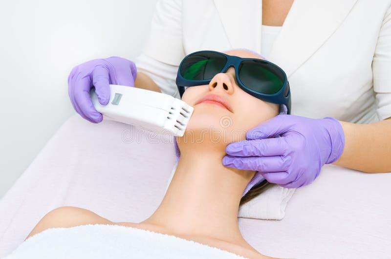 Jeune femme recevant le traitement de laser d'epilation images libres de droits