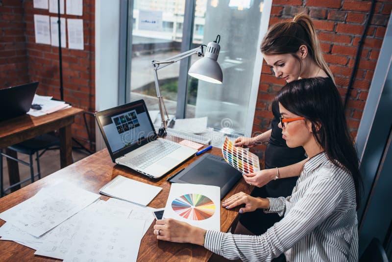 Jeunes femmes travaillant à un nouveau web design utilisant des échantillons de couleur et aux croquis se reposant au bureau dans photographie stock
