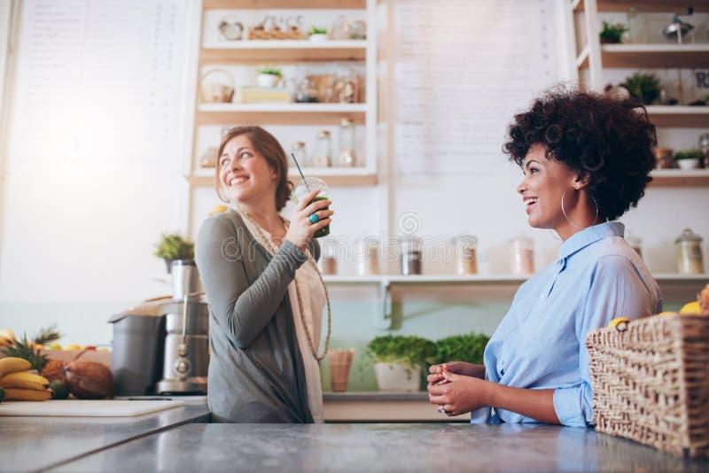 Jeunes femmes travaillant au bar à jus de fruit images stock