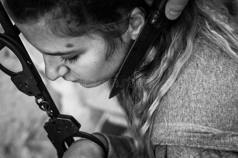 Jeunes femmes verrouillées avec des menottes au radiateur photographie stock libre de droits