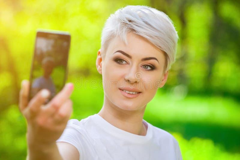 Jeunes, fille blonde attirante avec les cheveux courts faisant le selfie photographie stock libre de droits