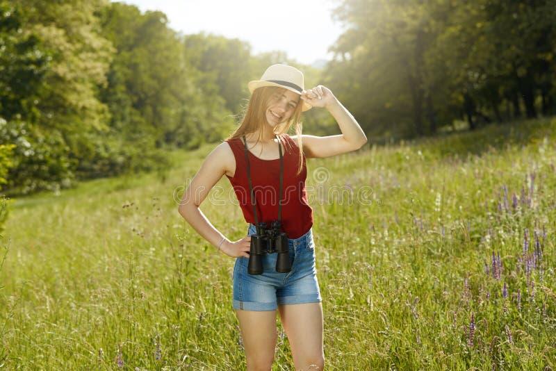 Jeunes fille sur la nature avec le chapeau et binoculaire Été photo libre de droits