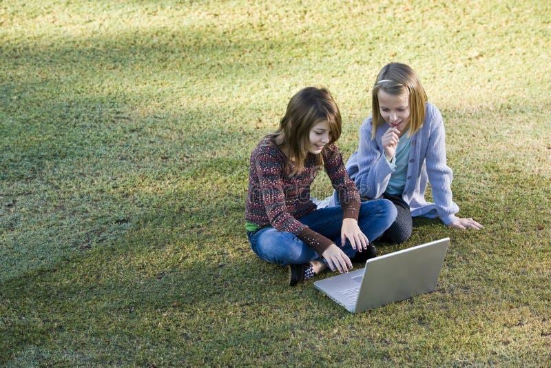Jeunes filles à l'aide de l'ordinateur portatif sur l'herbe photos libres de droits