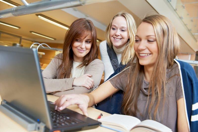Jeunes filles d'étudiant travaillant avec l'ordinateur portatif dans la bibliothèque image libre de droits