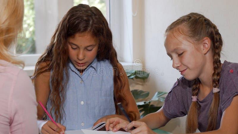 Jeunes filles dessinant à la classe d'art, montrant leurs travaux au professeur image libre de droits