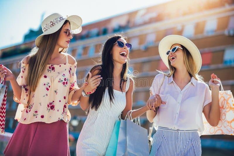Jeunes filles marchant la rue avec des sacs à provisions Achats heureux avec des sourires images stock
