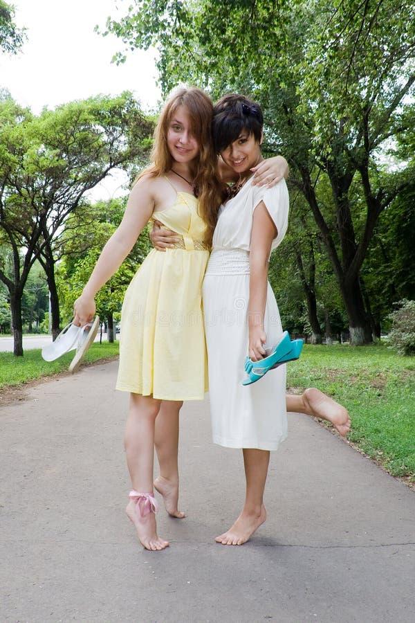 Jeunes filles marchant nu-pieds en stationnement image libre de droits
