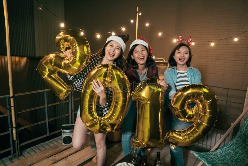 Jeunes filles montrant 2019 ballons sur le toit image libre de droits