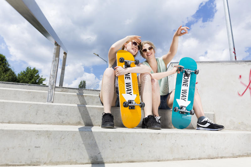 Jeunes filles s'asseyant sur les escaliers avec des planches à roulettes photos stock