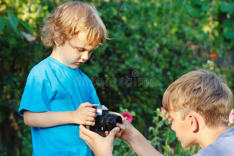 Jeunes frères blonds avec un appareil-photo à l'extérieur photo stock