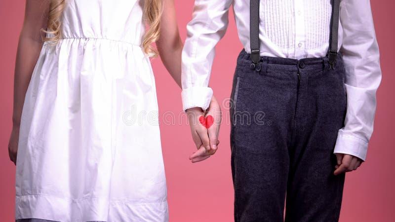 Jeunes garçon mignon et fille tenant des mains étroitement, première passion, jour de valentines de saint photo stock