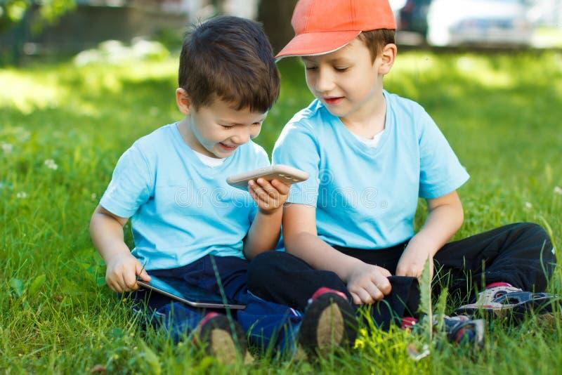 Jeunes garçons avec le smartphone et le comprimé sans fil image libre de droits