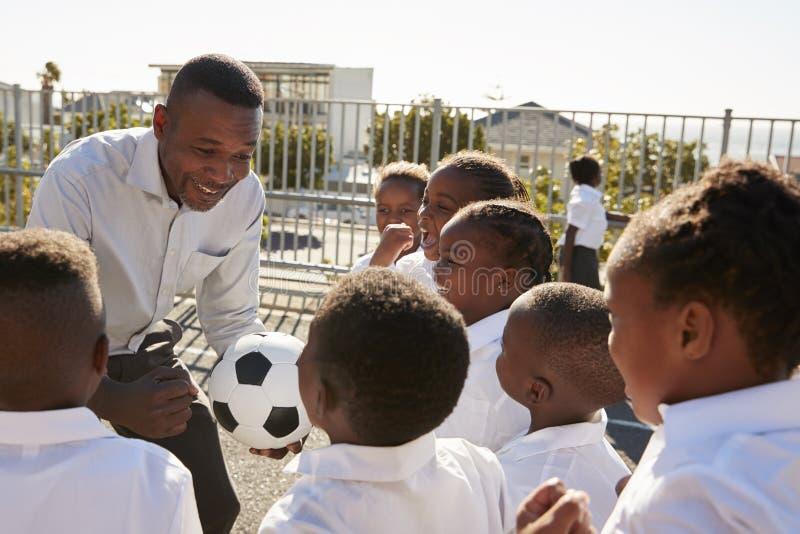 Jeunes garçons dans un terrain de jeu d'école avec le professeur tenant la boule photos stock
