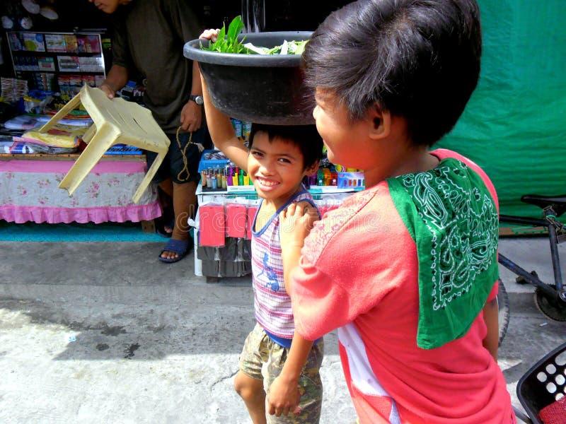 Jeunes garçons sur un marché du cainta, rizal, Philippines vendant des fruits et légumes image stock