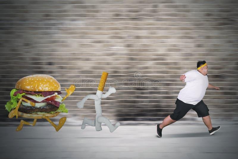 Jeunes grosses courses d'homme de cigarette et d'hamburger photographie stock libre de droits