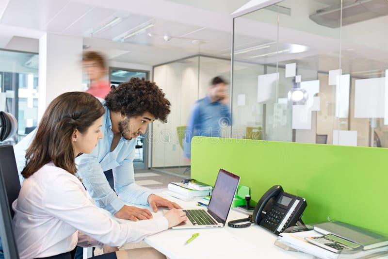 Jeunes homme d'affaires et femme d'affaires à l'aide de l'ordinateur portable au bureau dans le bureau photos libres de droits