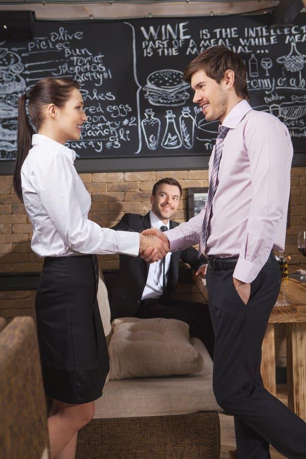 Jeunes homme d'affaires et femme d'affaires attirants au café photos stock