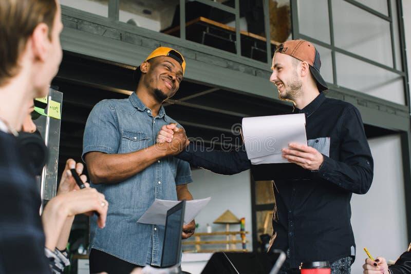 Jeunes hommes africains et caucasiens créatifs se serrant la main au cours de la réunion de travail dans le bureau Travail d'équi photographie stock