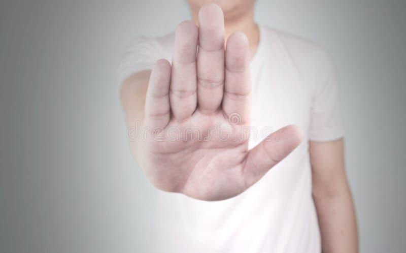 Jeunes hommes asiatiques portant un signe d'arrêt d'exposition de main de T-shirt d'isolement sur le fond blanc photographie stock