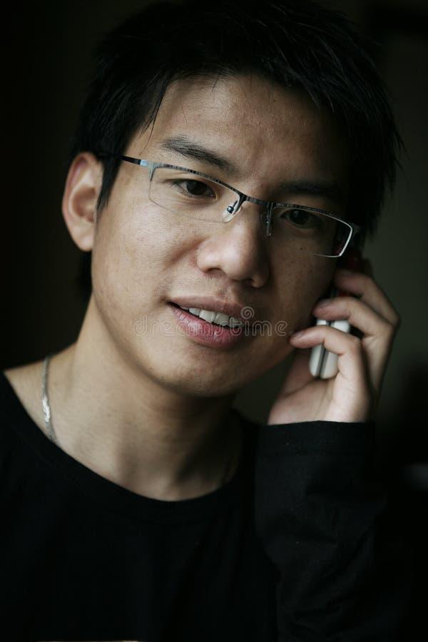 Jeunes hommes asiatiques sur appeler images stock
