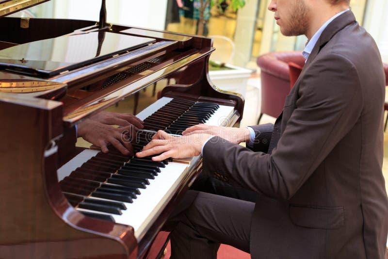 Jeunes hommes beaux jouant le piano au restaurante images stock