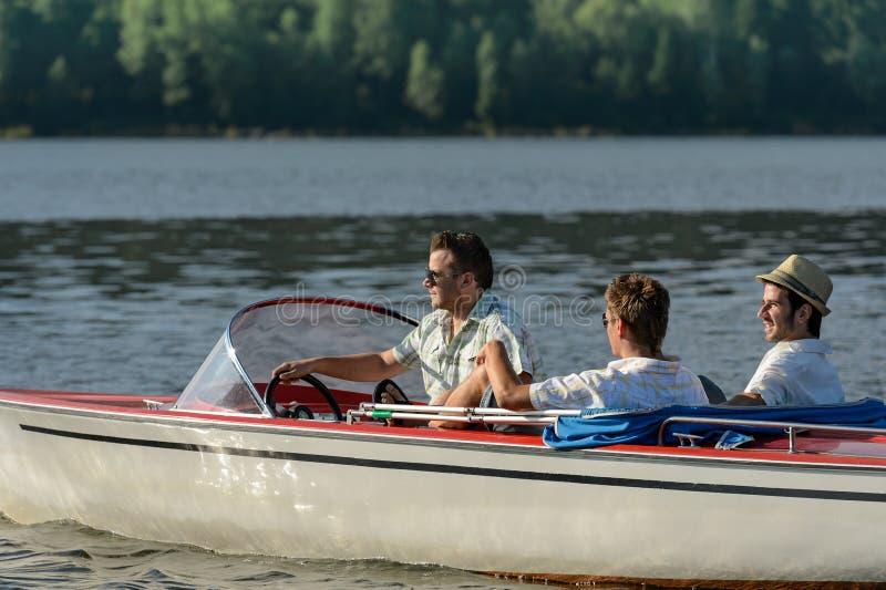 Hommes conduisant le bateau de vitesse appréciant le soleil images stock