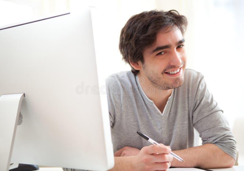 Jeunes hommes décontractés écrivant au bureau images stock