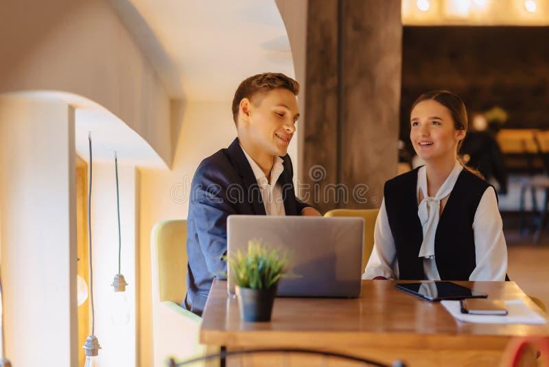 Jeunes hommes d'affaires gar?on et travail de fille avec un ordinateur portable, un comprim? et des notes dans le caf? photographie stock