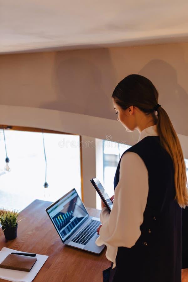 Jeunes hommes d'affaires gar?on et travail de fille avec un ordinateur portable, un comprim? et des notes dans le caf? images stock