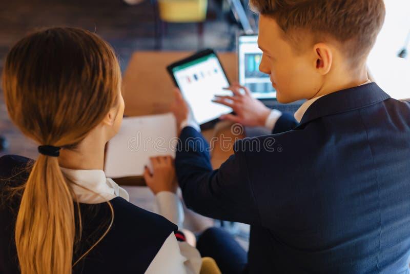 Jeunes hommes d'affaires gar?on et travail de fille avec un ordinateur portable, un comprim? et des notes dans le caf? image stock