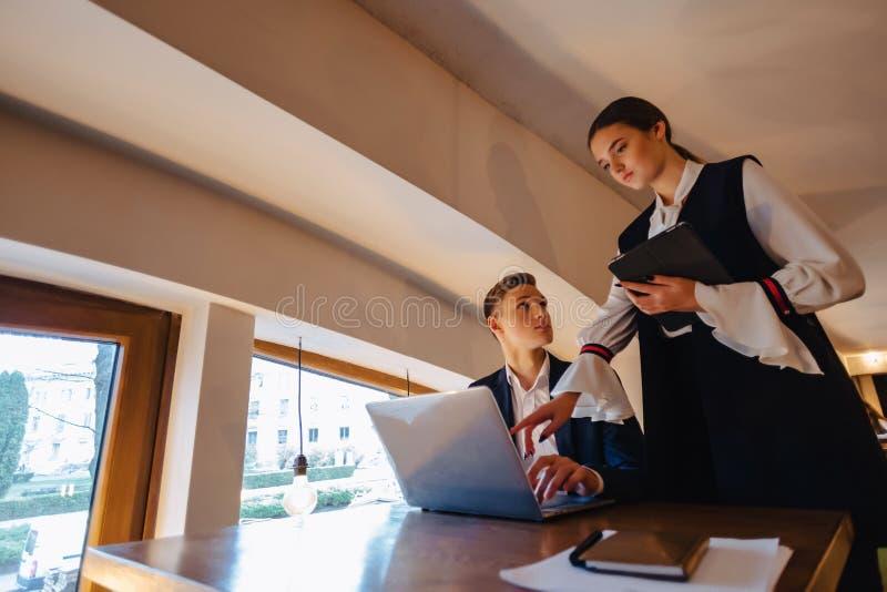 Jeunes hommes d'affaires gar?on et travail de fille avec un ordinateur portable, un comprim? et des notes dans le caf? image libre de droits