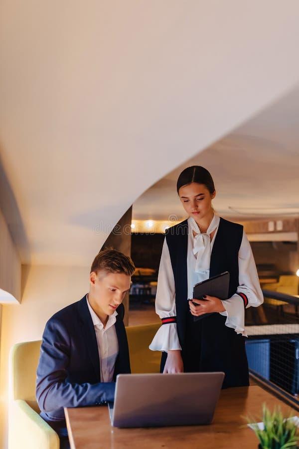 Jeunes hommes d'affaires gar?on et travail de fille avec un ordinateur portable, un comprim? et des notes dans le caf? photos libres de droits