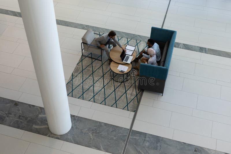 Jeunes hommes d'affaires multi-ethniques travaillant dans le lobby images stock