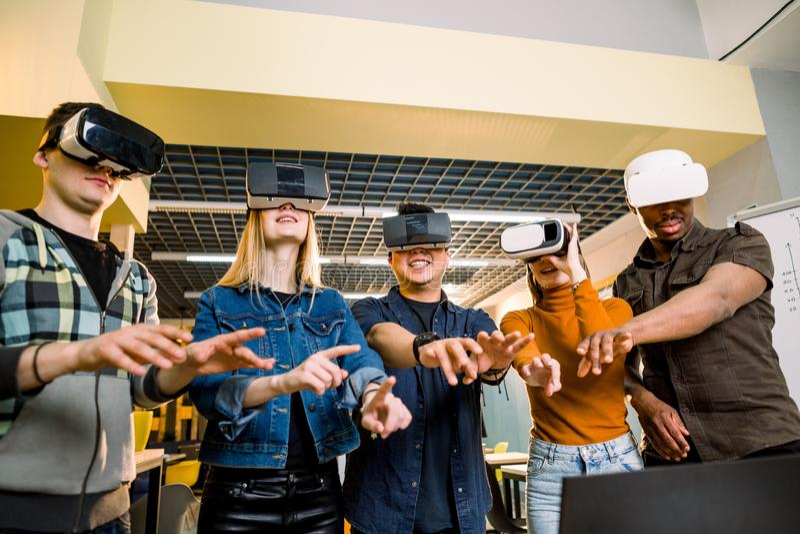 Jeunes hommes d'affaires multiraciaux portant des lunettes de réalité virtuelle avec toucher l'air pendant la conférence de réuni image stock