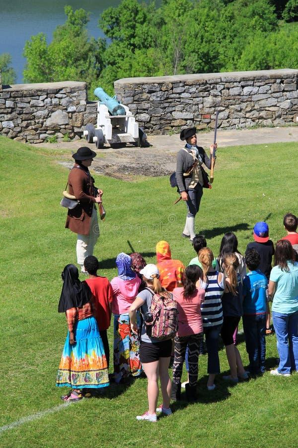 Jeunes hommes dans l'uniforme du soldat, instruisant le groupe de visite sur l'histoire du fort Ticonderoga, New York, 2014 images stock
