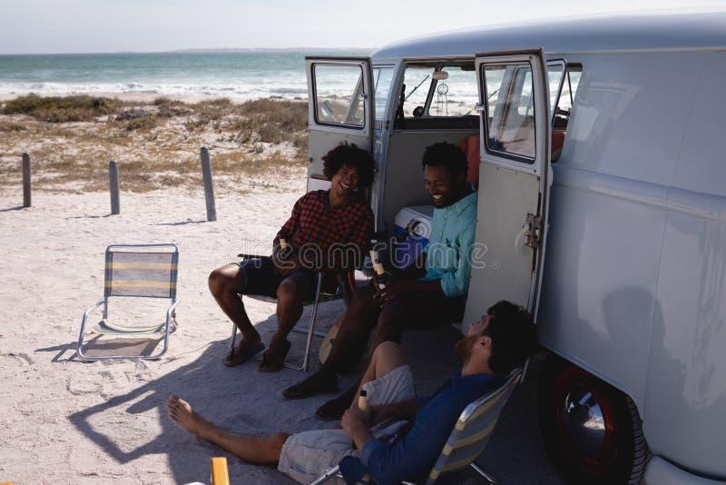 Jeunes hommes heureux détendant près du camping-car à la plage au soleil images libres de droits