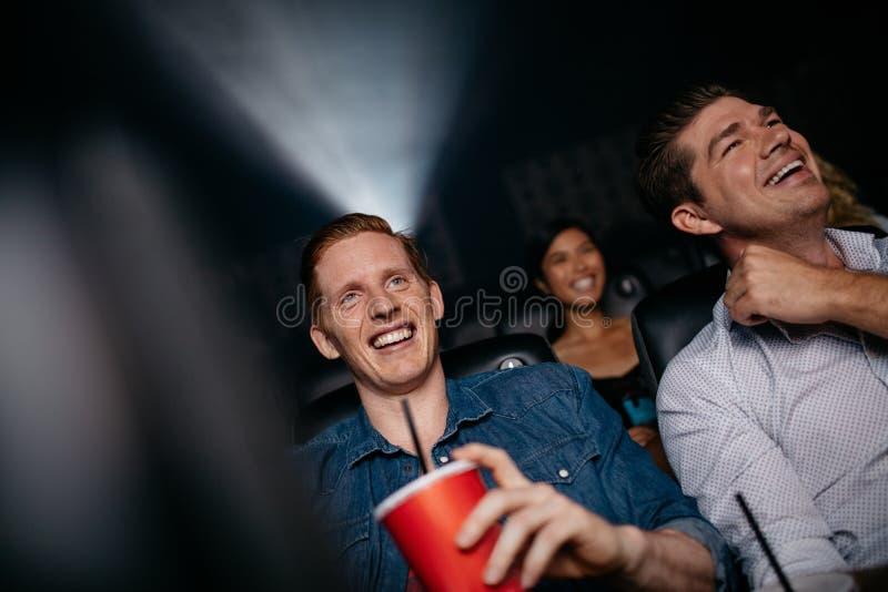 Jeunes hommes observant le film dans le cinéma images stock