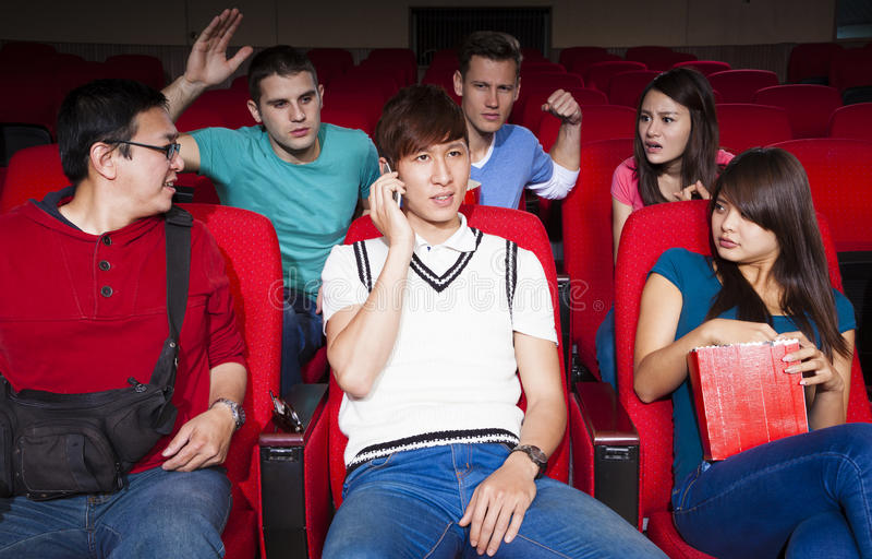 Jeunes hommes parlant au téléphone tout en observant le film photographie stock libre de droits