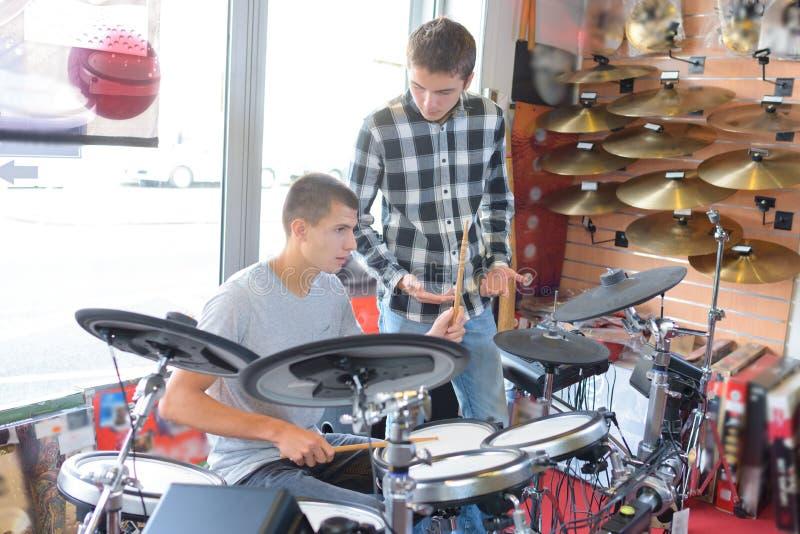 Jeunes hommes regardant le kit électronique de tambour photographie stock