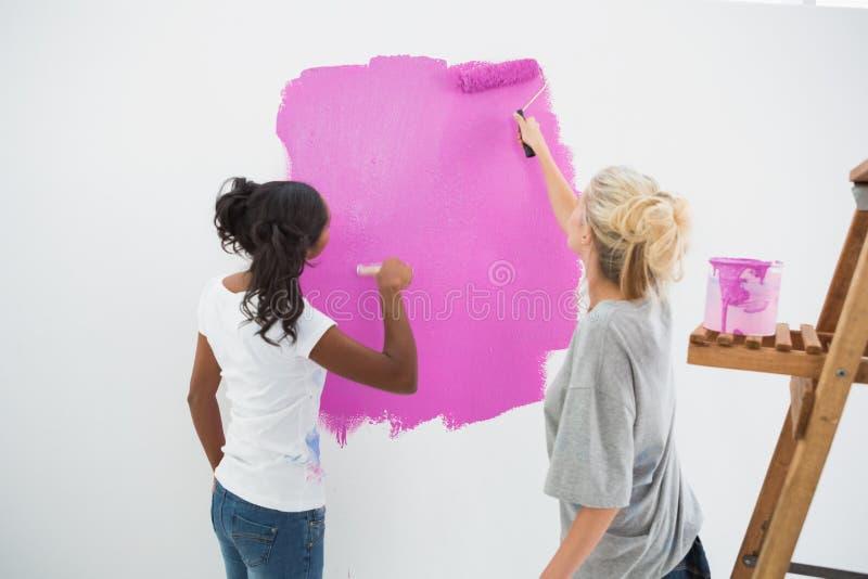 Jeunes housemates heureux peignant le rose de mur images libres de droits