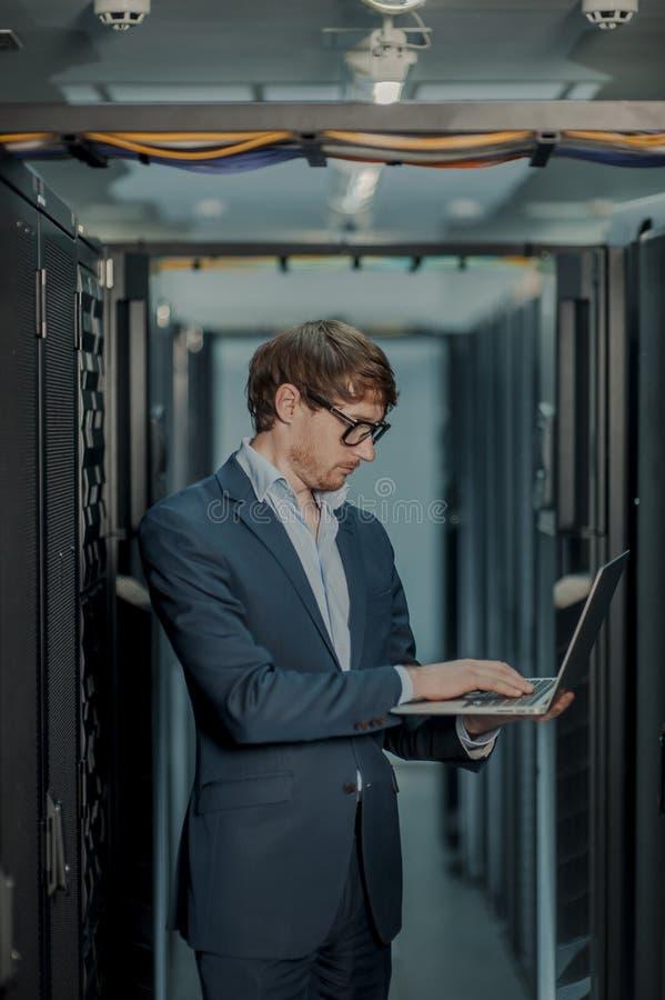Jeunes il homme d'affaires d'ing?nieur avec l'ordinateur portable en aluminium moderne mince dans la chambre de serveur de r?seau images stock