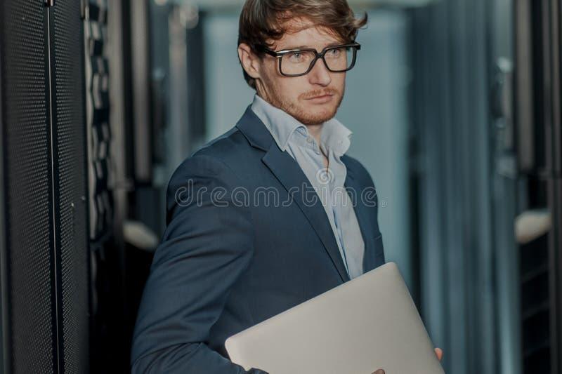 Jeunes il homme d'affaires d'ing?nieur avec l'ordinateur portable en aluminium moderne mince dans la chambre de serveur de r?seau photographie stock libre de droits